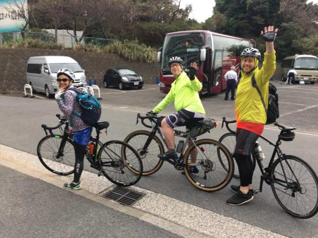Three cyclists wave before departing
