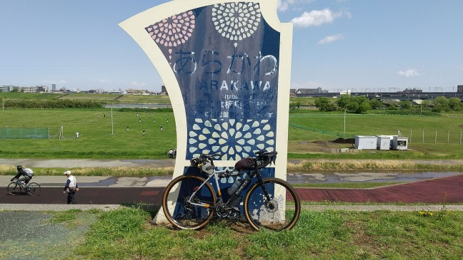 Bicycle in front of sign for Arakawa cycling course