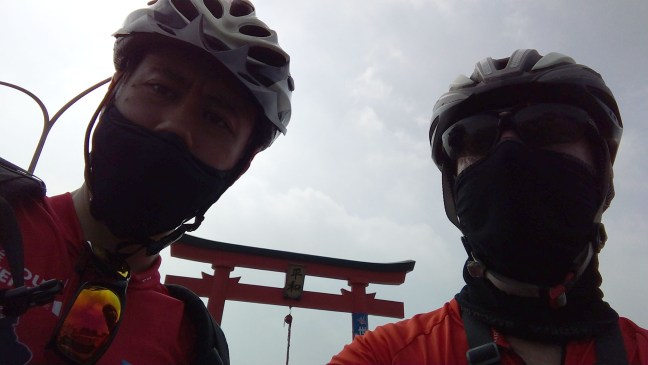 Selfie of two cyclists in helmets and masks in front of Japanese shrine torii