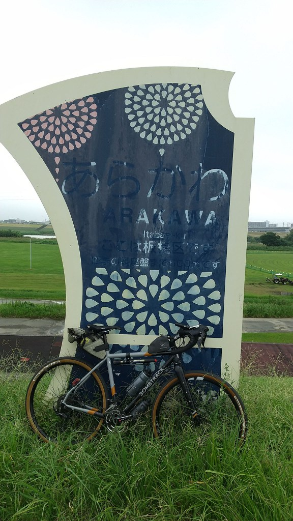 Bicycle leaning against sign for Arakawa river