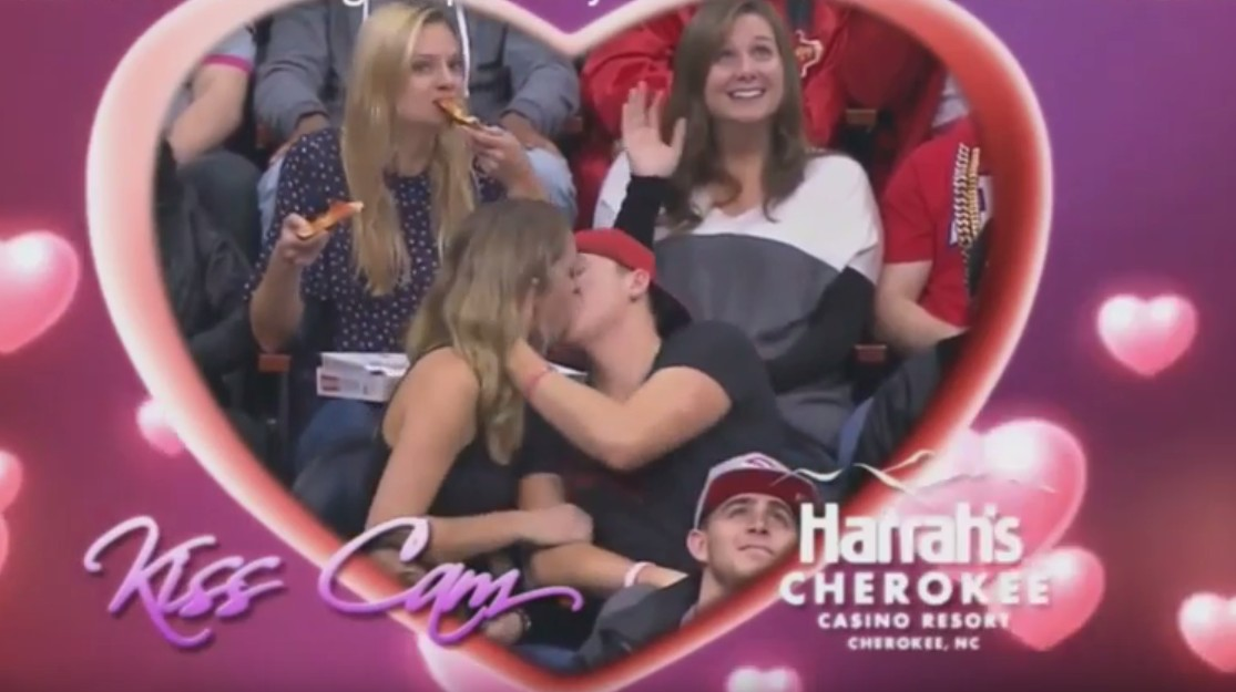 Girl double fists pizza on kiss-cam and becomes the hero we all deserve