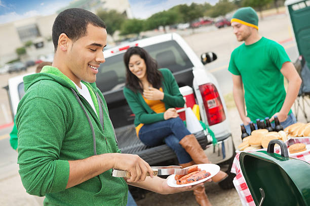 Young man grilling during tailgating party near football stadium.