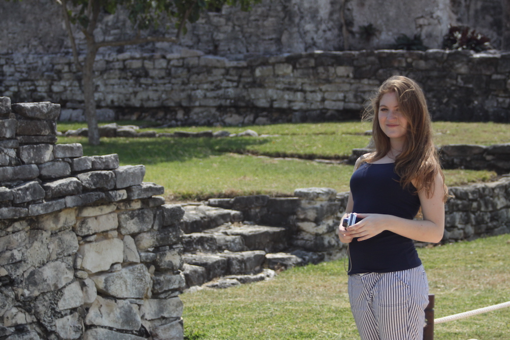 Girl stands among Tulum Mayan Ruins
