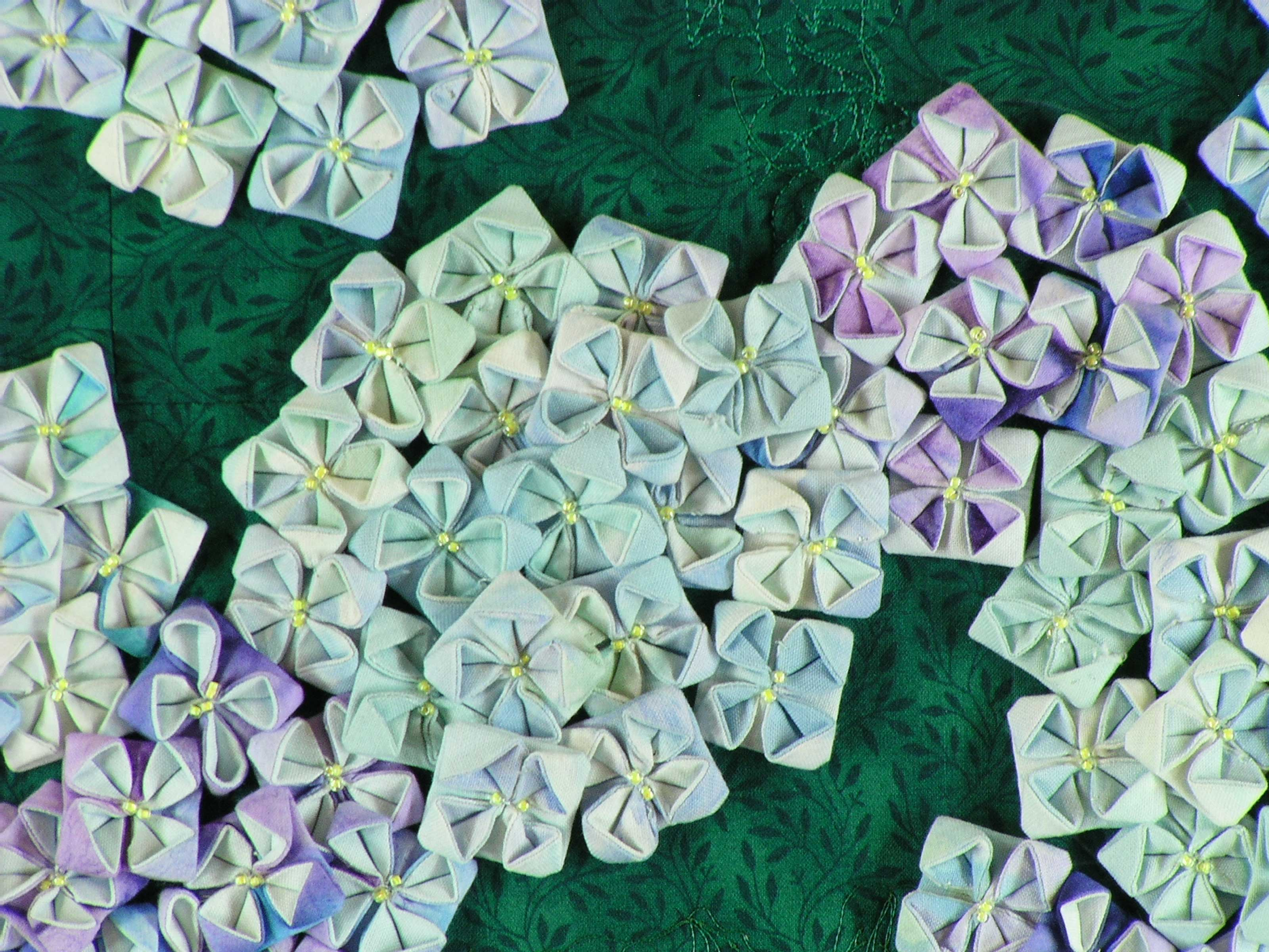 Hydrangea blossoms created by folding numerous squares of handprinted fabric.