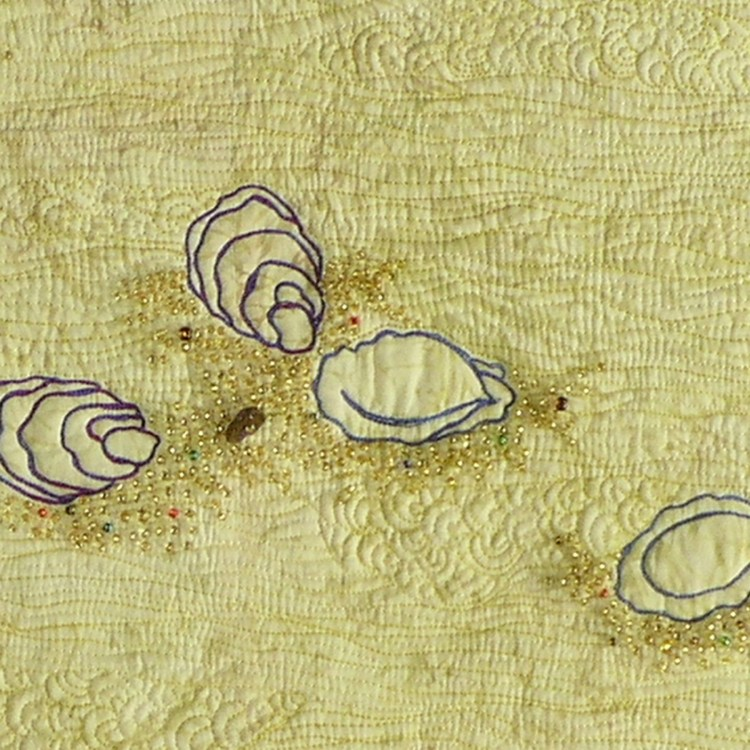 Detail includes several thread painted oyster shells nestled amongst gold colored beads