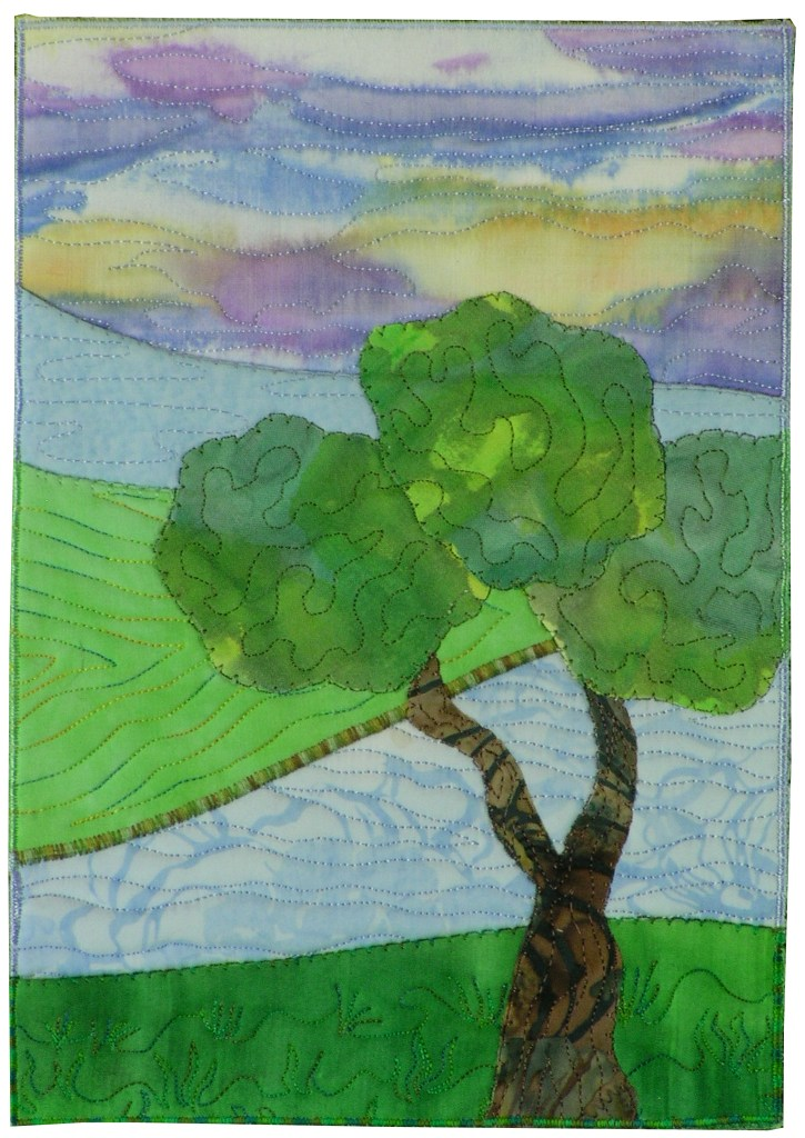 Multi layers of fabric creating a salt marsh landscape are pre quilted. This provides dimensionality to the piece. There is a tree with a twisted trunk in the foreground