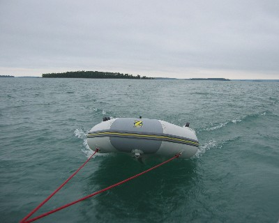 Photo: Zodiac dinghy in tow leaving Drummond Island, Michigan. Credit: L. Borre.