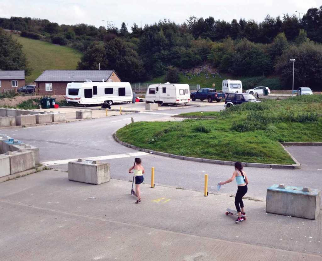 Picture of children playing on a site on scooters and skateboard