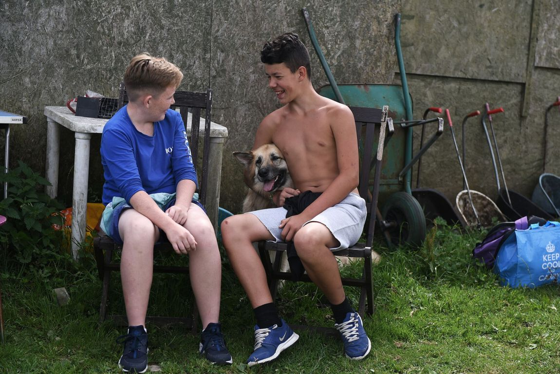 Picture of two boys smiling with a dog