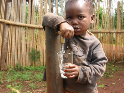 Child drinking from a drinking water supply tap. Cameroon .