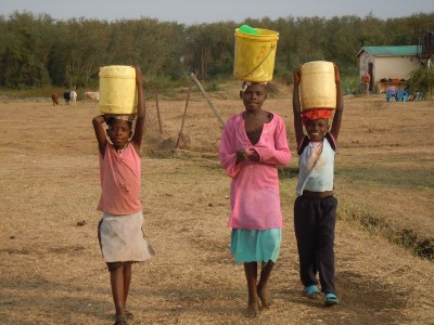Young carrying water. Kenya.