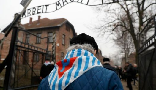 "Survivors and guests walk past the ""Arbeit Macht Frei"" gate at the former Nazi German concentration and extermination camp Auschwitz, during the ceremonies marking the 73rd anniversary of the liberation of the camp and International Holocaust Victims Remembrance Day, in Oswiecim, Poland, January 27, 2018. REUTERS/Kacper Pempel"