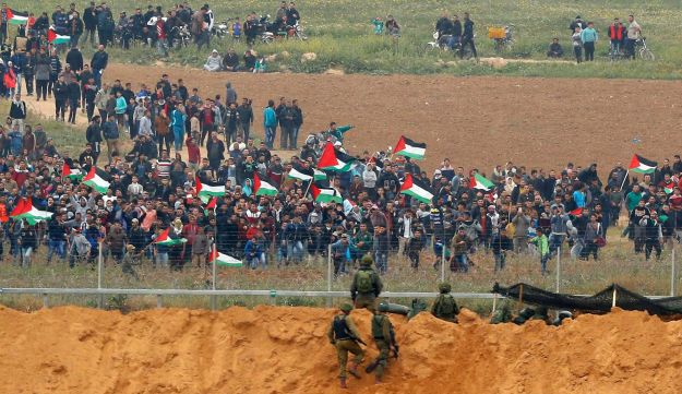Palestinian demonstrators face IDF soldiers near the fence in the northern Gaza Strip, March 30, 2018.