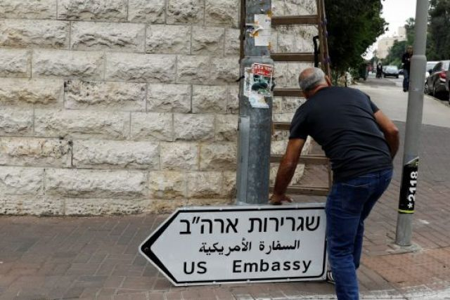 A worker holds a road sign directing to the U.S. embassy, in the area of the U.S. consulate in Jerusalem, May 7, 2018. REUTERS/Ronen Zvulun