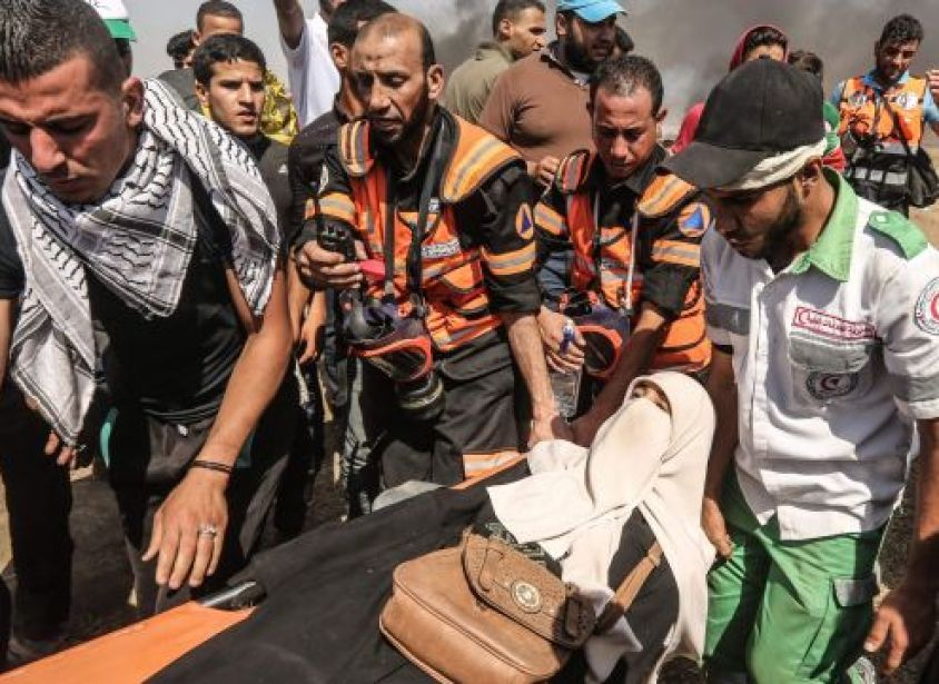 Palestinian protesters and paramedics carry a woman on a stretcher away from the scene of clashes with Israeli forces along the Israel-Gaza border on June 8, 2018.