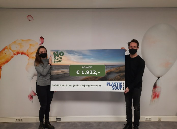 Ondernemer Ernst-Jan Koole overhandigt de anderhalve meter lange corona-proof cheque aan Milou de Ruig van de Plastic Soup Foundation.