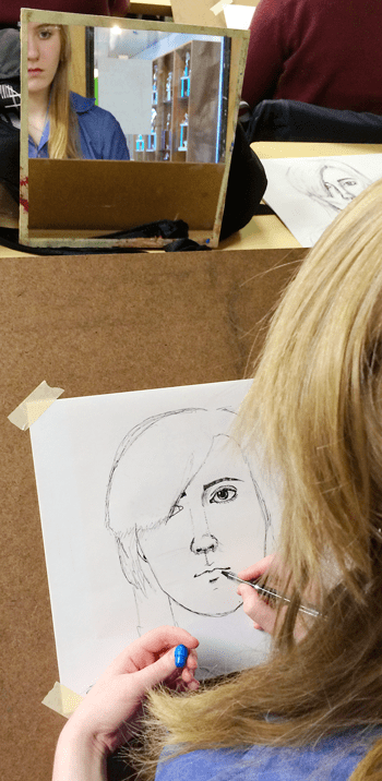 Scholar draws a self portrait during art class