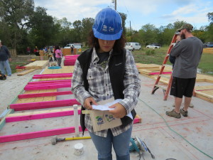 Madeline checking the wall raising plans at a Habitat build in Bryan.