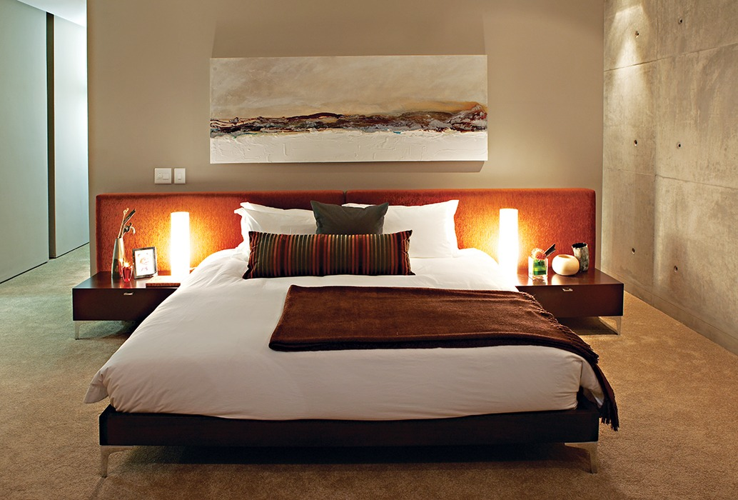The generous proportions of the low-slung upholstered headboard encompass the entire width of the bed and the bedside pedestals.