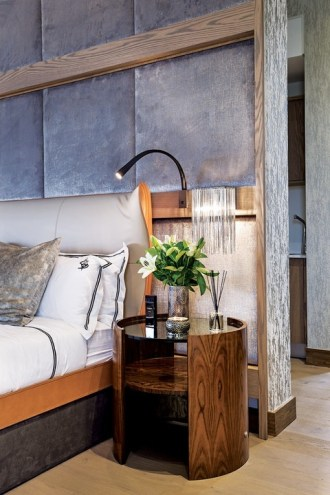 The pronounced winged headboard sits in front of a velvet padded wall and is flanked by circular bedside pedestals.
