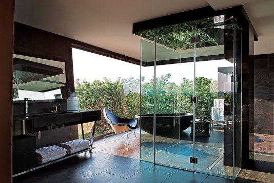 The black bath tub is adjacent to a clear glass window, which is bordered by trees. The indigenous grounds form a major part of the atmosphere of this home in effecting the feel of being deep in a forest.
