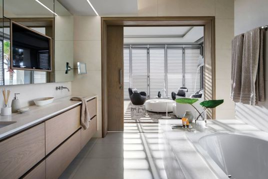 In the main suite the large mirror wall reflects the sea views and features a small tea / coffee prep space, desk and work area, plus full height linen cupboard with cedar shelves for storage. Sanitaryware by Flush Bathrooms.
