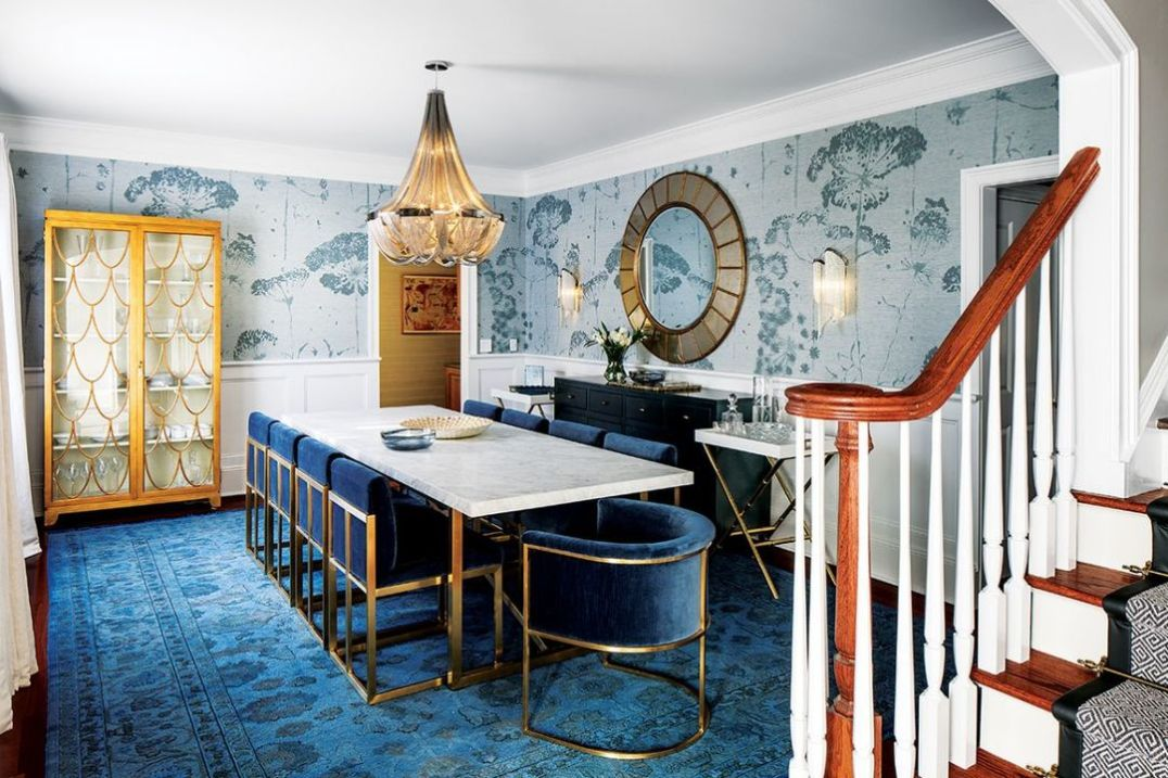 The formal dining room has a Torano marble dining table. There are eight dining chairs in indigo velvet and brass, plus two additional Wexler Barrelback chairs at the table ends. The strikingly bold rug is a vintage piece.