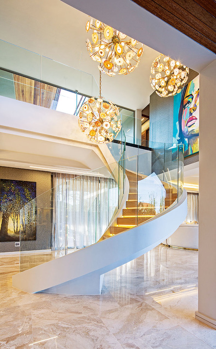 Agate Stone-finished Branquinho lights hang over the spiral staircase.