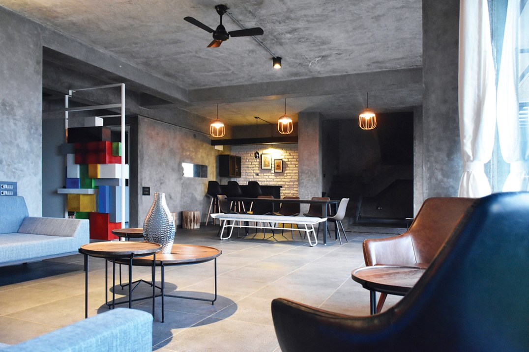 Industrial, contemporary interior design with local flair. The grey shell of this penthouse is a foil for a bold use of colour seen in lighting and the block sculpture wall.