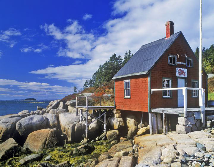 A red lobster house on the rocky coast on a summer day.