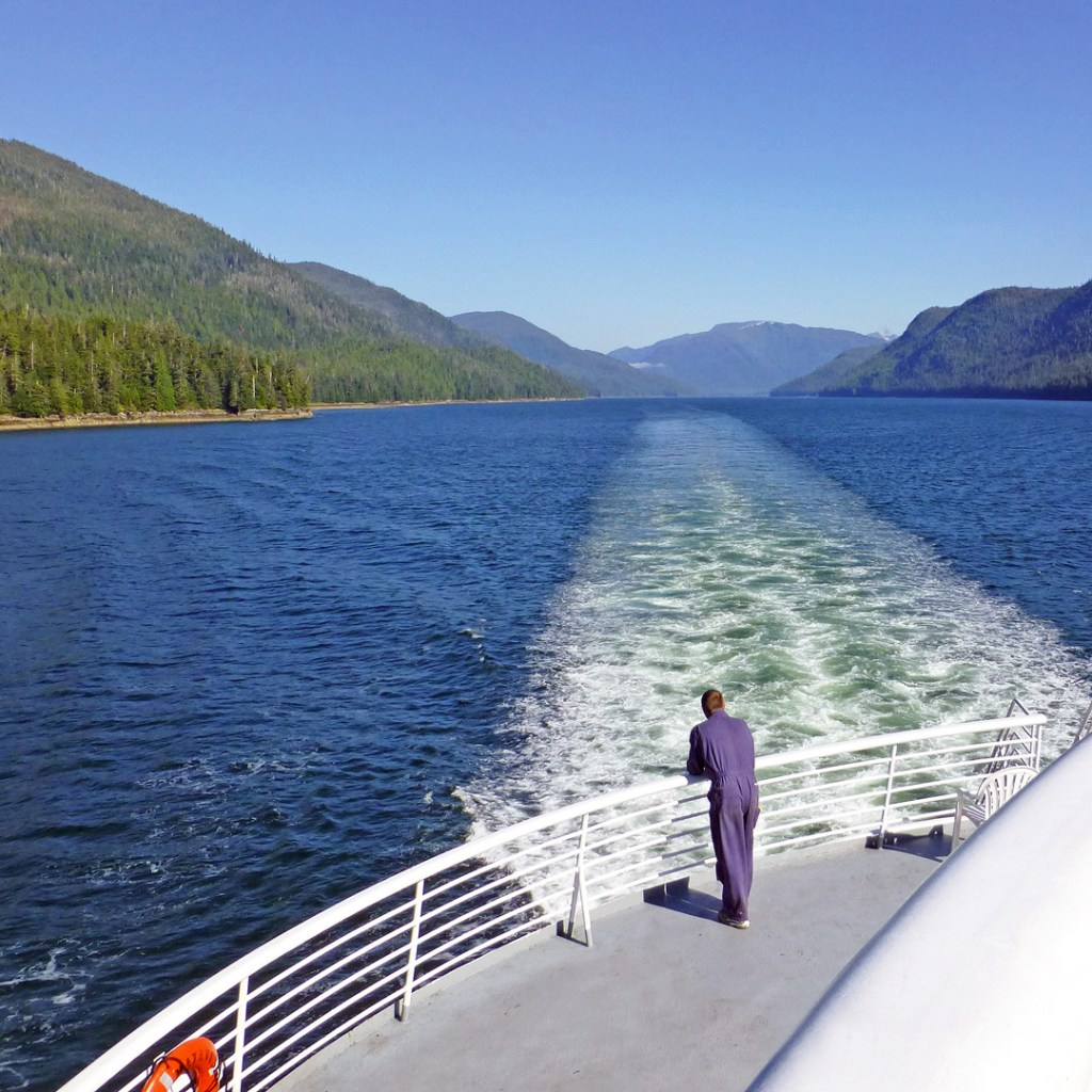man standing on a ferry looking out at Alaskan scenery