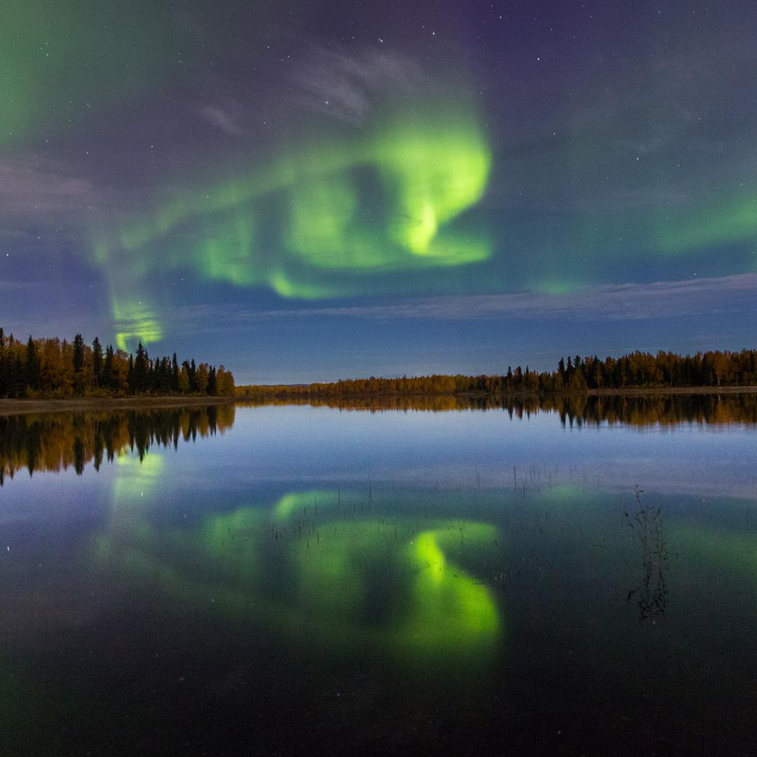 bright green aurora over a lake in Alaska