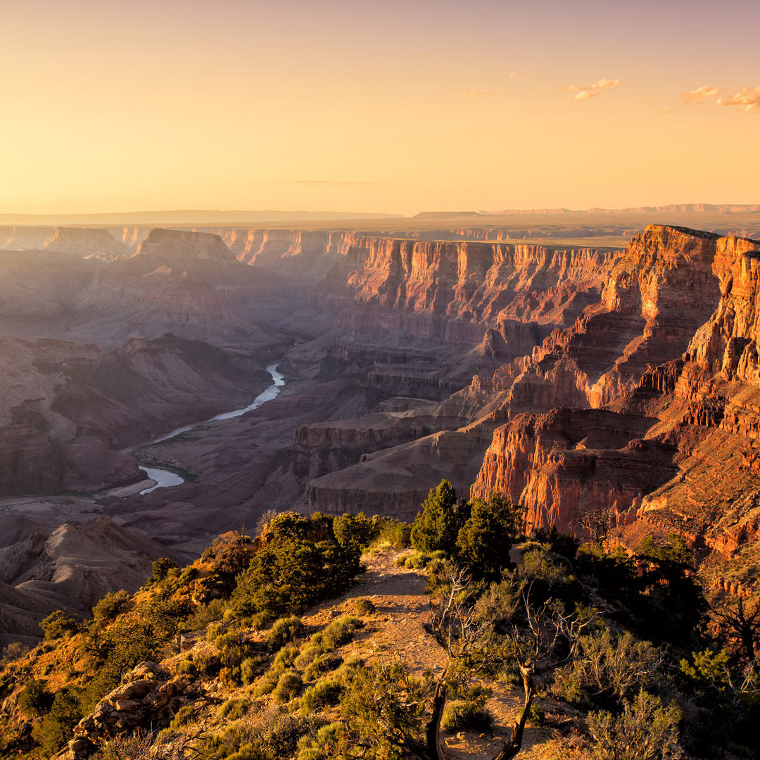 sunset lights up the sky over the Grand Canyon