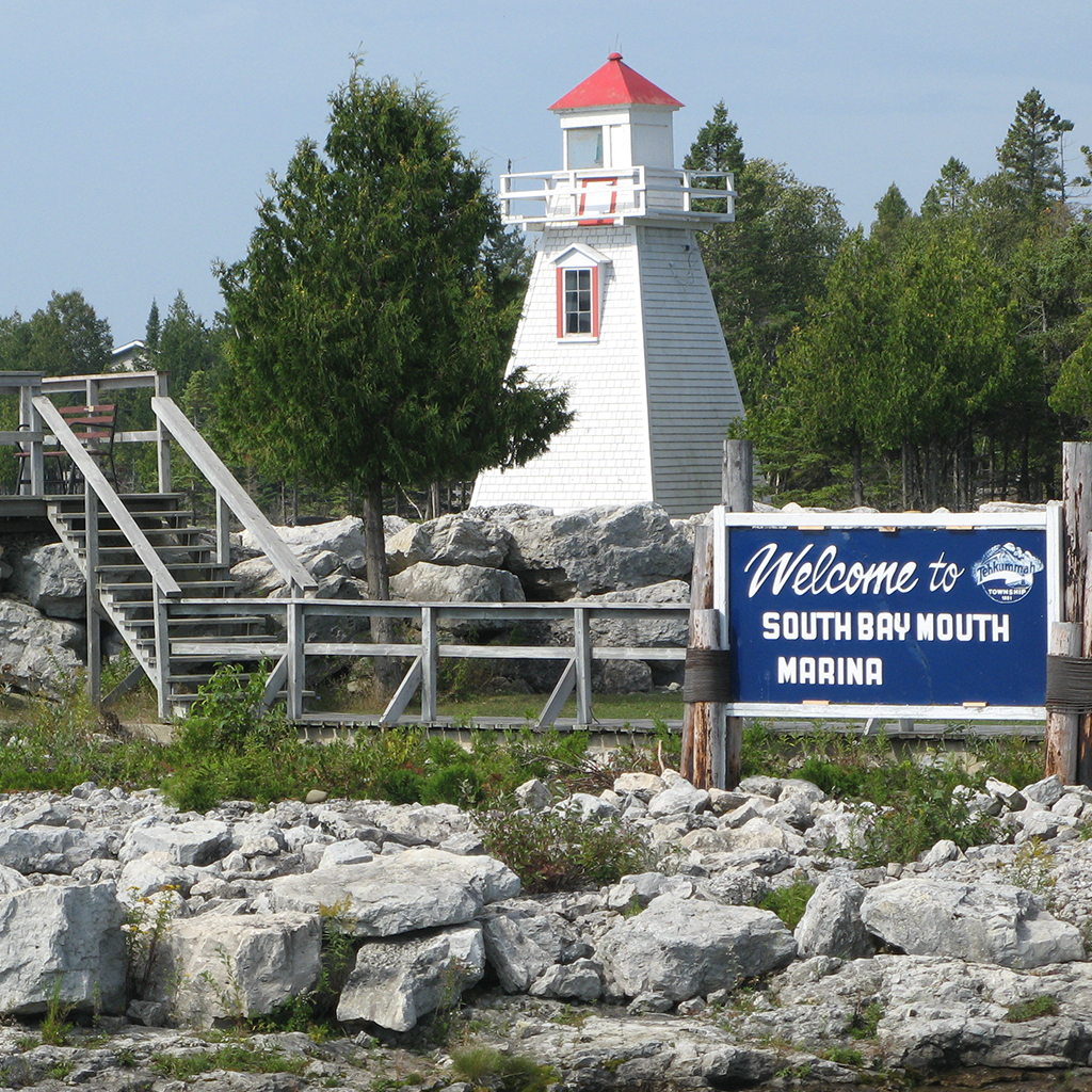 A lighthouse stands on a rocky and grassy island with a sign in front that reads Welcome to South Bay Mouth Marina