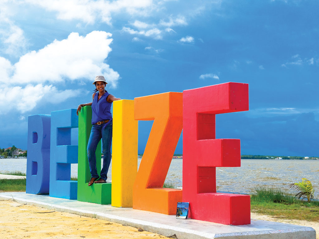 woman posing with the Belize sign