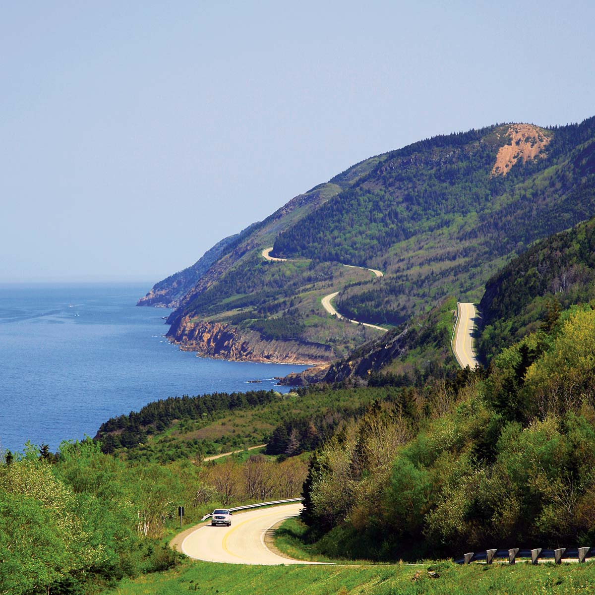 A car traverses the windy coastal Cabot Trail highway in Cape Breton Highlands National Park.