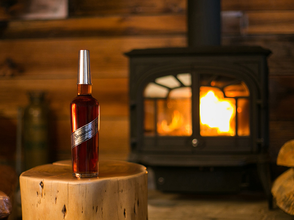 bottle of snowflake whiskey from Stranahans by the fire