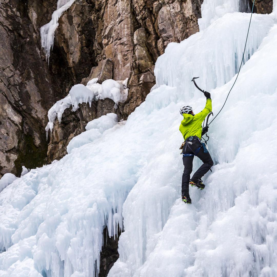 man ice climbing frozen falls in Colorado