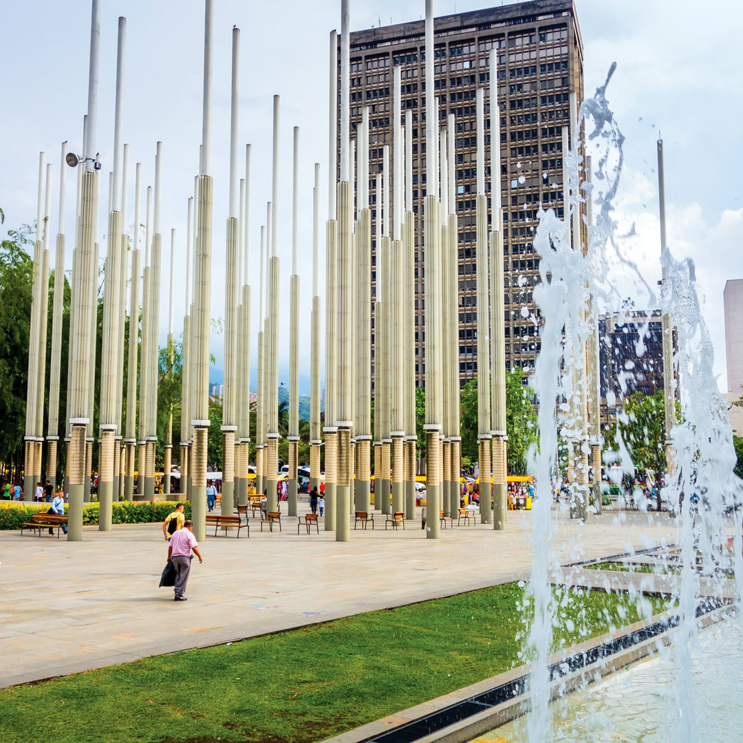 a fountain flowing in front of the spires of Parque de las Luces in Medellin