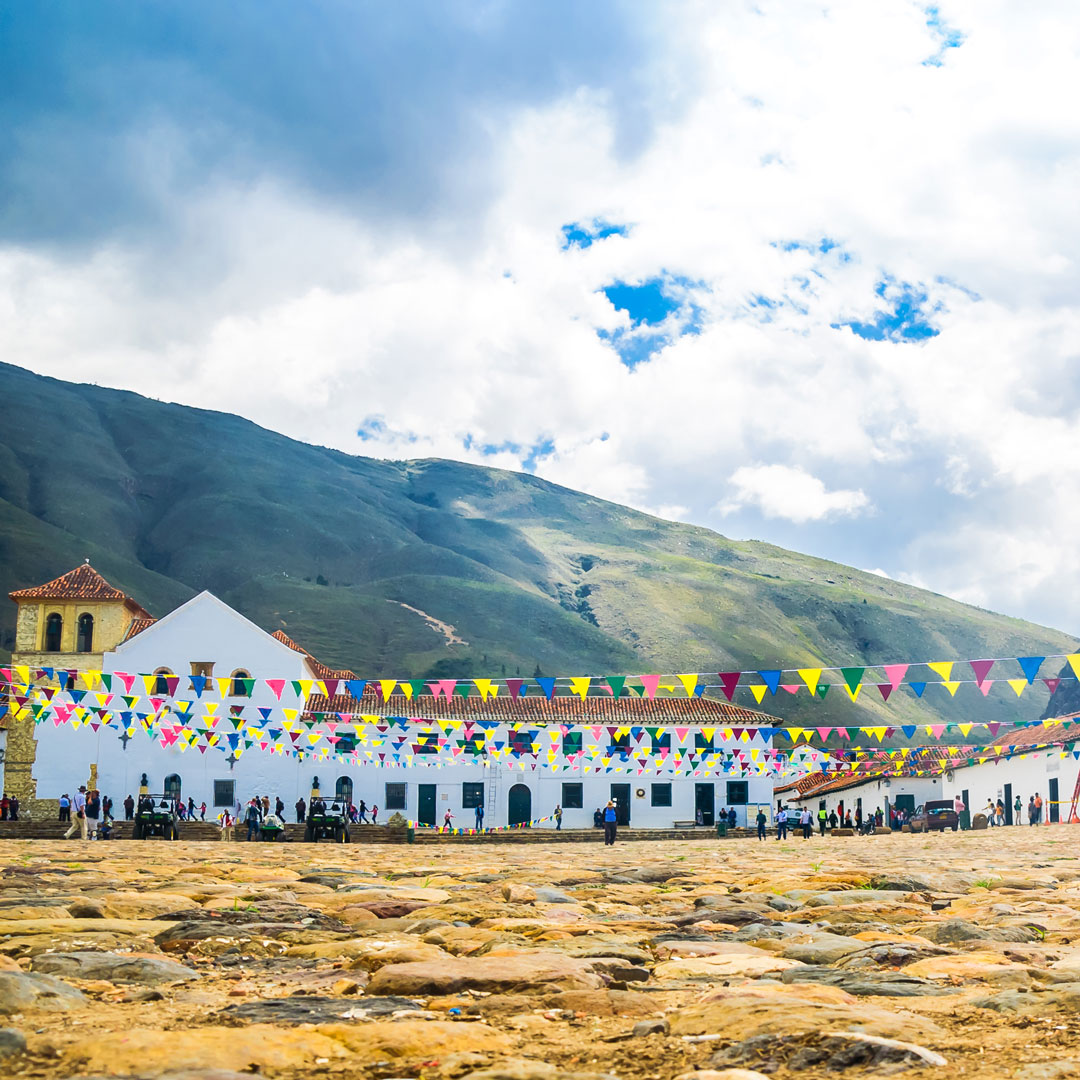 colorful flags surround colonial buildings in Villa de Leyva's central plaza