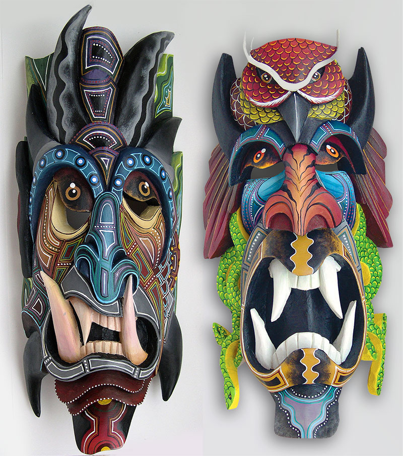 A pair of colorful and intricately carved Boruca masks with large teeth and devilish features.