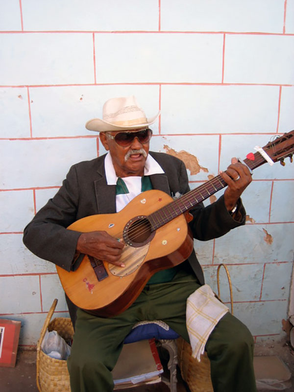a man in a hat and sunglasses playing a guitar