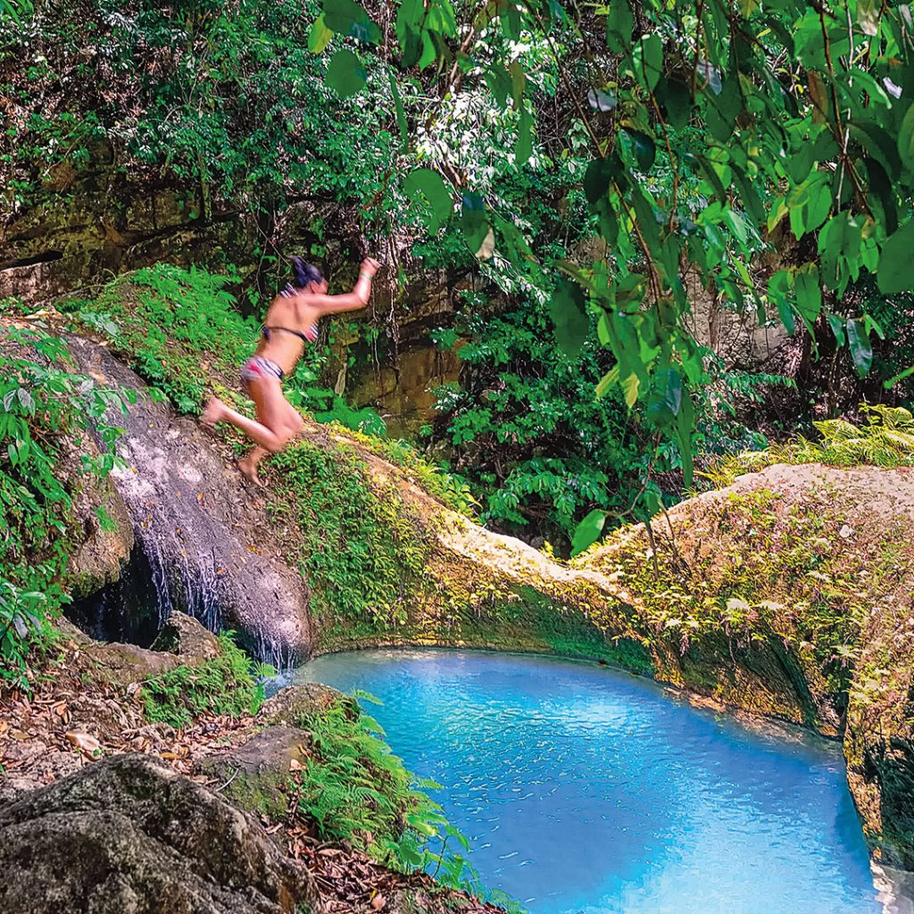 a woman jumping into a bright blue pool in a forest setting