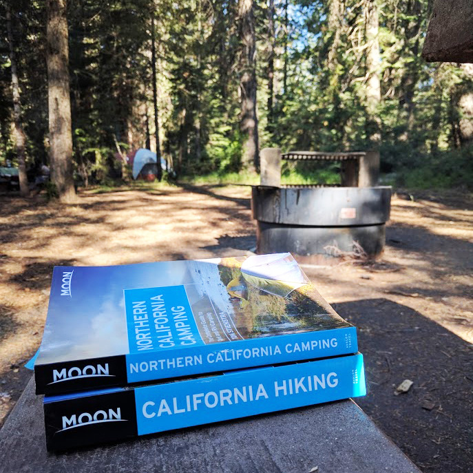 Two Moon guidebooks (California Hiking and Northern California Camping) sit on a picnic table at Fowlers Camp, a fire pit and a distant tent are visible in the background