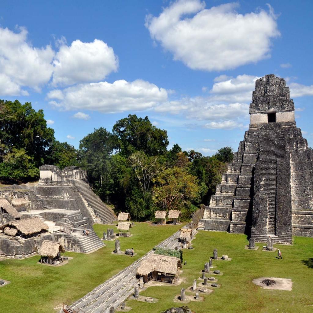 Tikal's Temple I and the grassy courtyard on a sunny day.