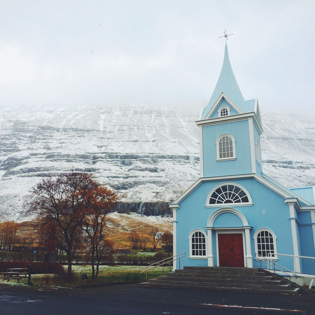 Bláa Kirkjan (Blue Church) with snow on the hillside beyond.