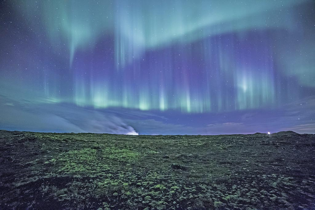 Northern Lights over a moss-covered lava field