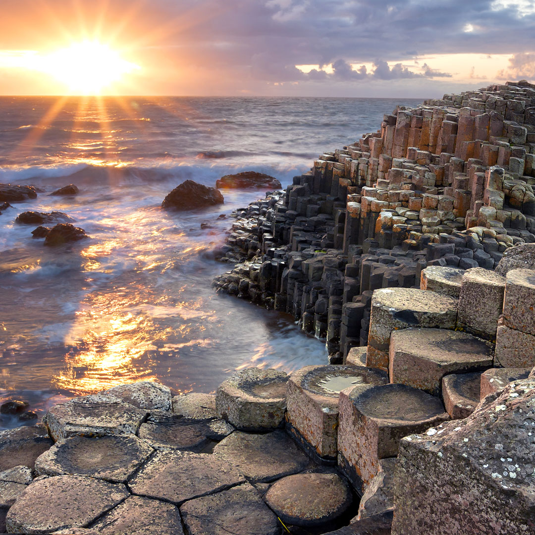 purple hues of sunset over the coastal area of Giant's Causeway in Ireland