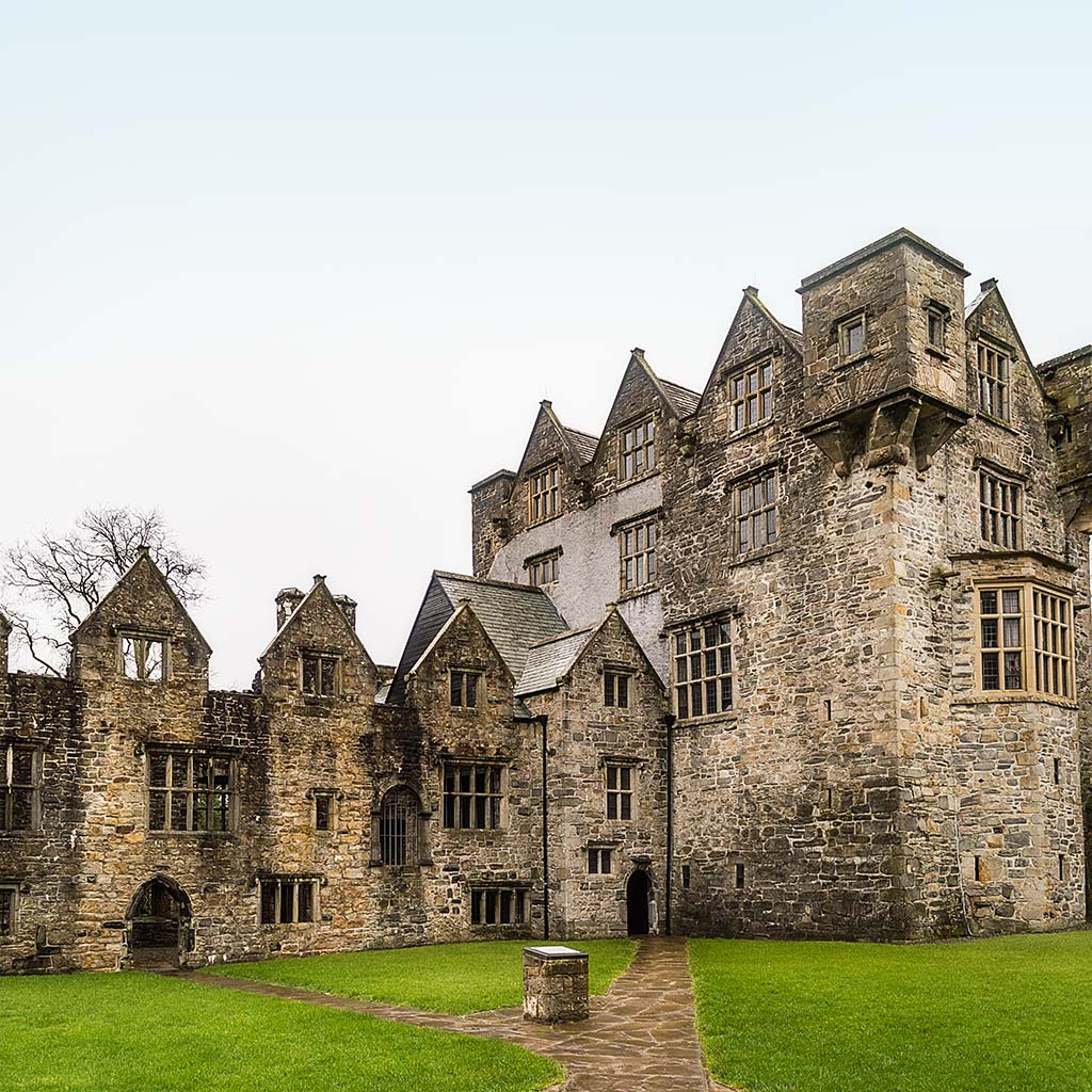 Amidst the walls of Donegal Castle, a stone walkway cuts through a low lawn.