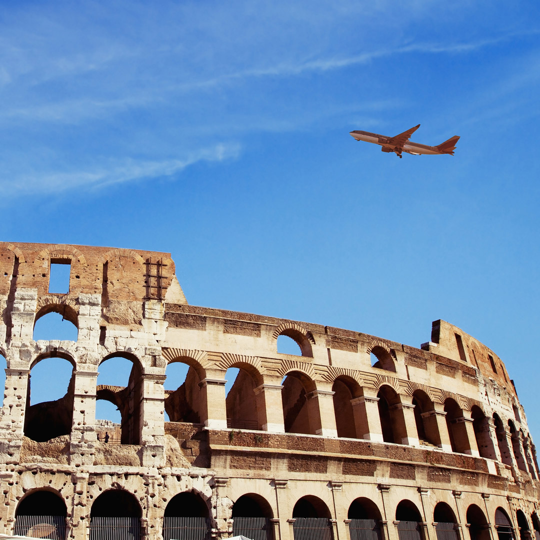 plane flying over the Coliseum in Rome, Italy